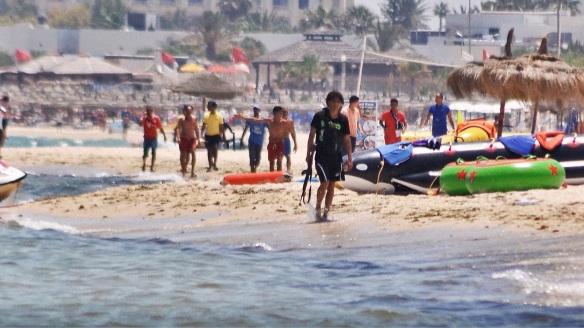PÅ VEI MOT DØDEN: På en nettside fremstår dette bilde av den bevæpnede terroristen som går langs stranden nesten som et vanlig feriemotiv. Med trykksverte forvandles det til et drepende sterkt dokument av terroristen med en hale av skuelystne etter seg. Foto: SKY NEWS, APTN